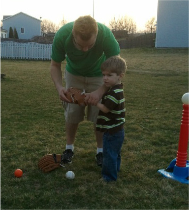 Daddy putting a baseball glove on Lucas